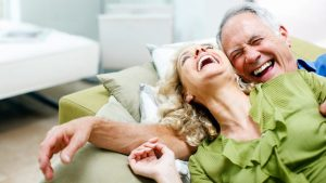 Older white couple laughing while leaning back on a green couch