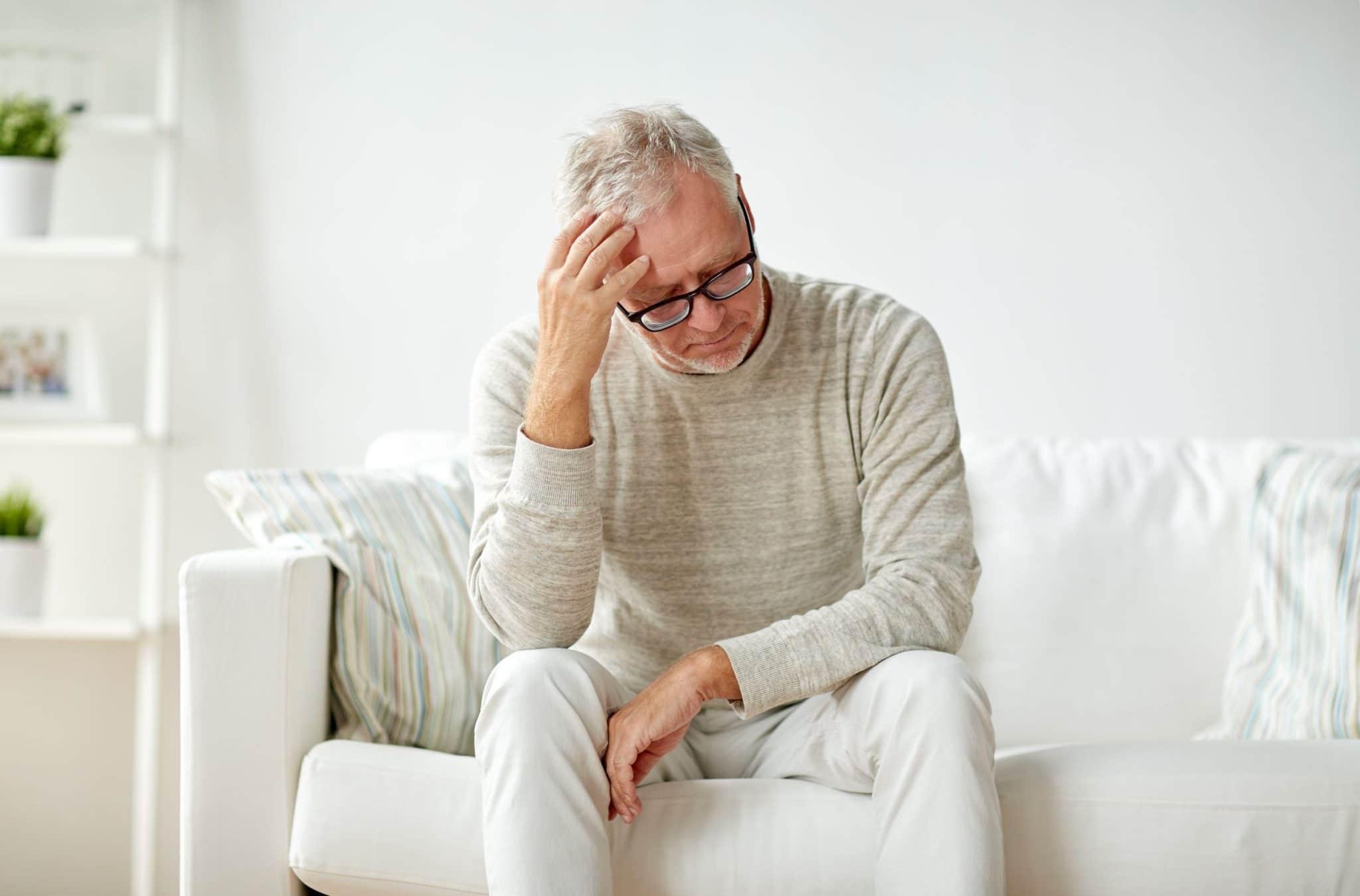 Worried Senior Man Sitting on Couch