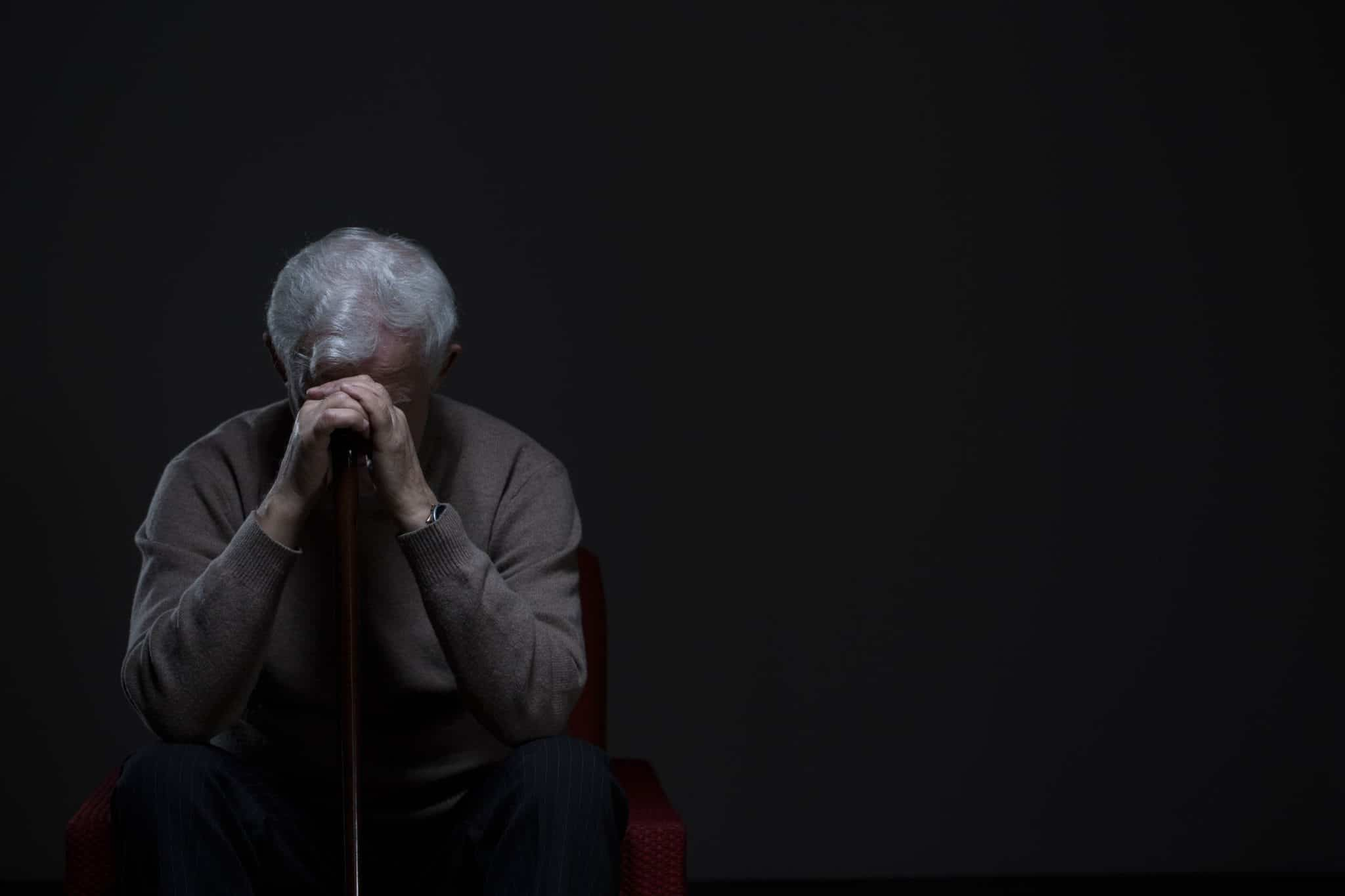 Older Man in Dark with Head in His Hands