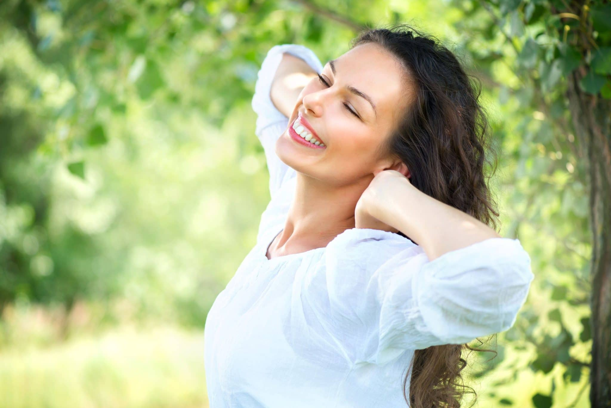 Woman Feeling Great from IV Vitamin Therapy Benefits While Smiling and Stretching Outdoors