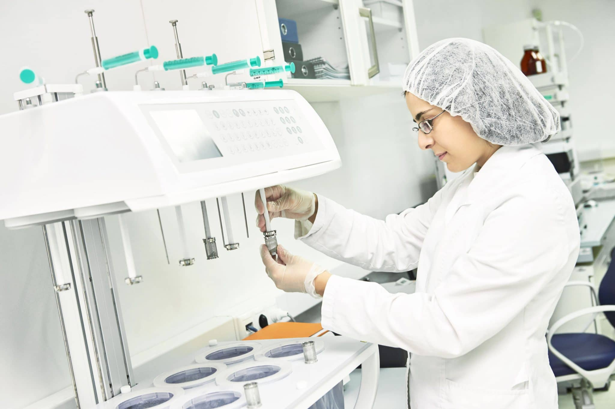 woman dressed in white lab coat and protective hairnet putting medication into a tube at a compounding pharmacy