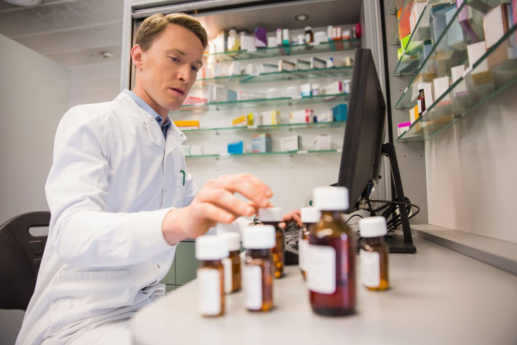 man with white lab coat counting bottles of medication at a compounding pharmacy