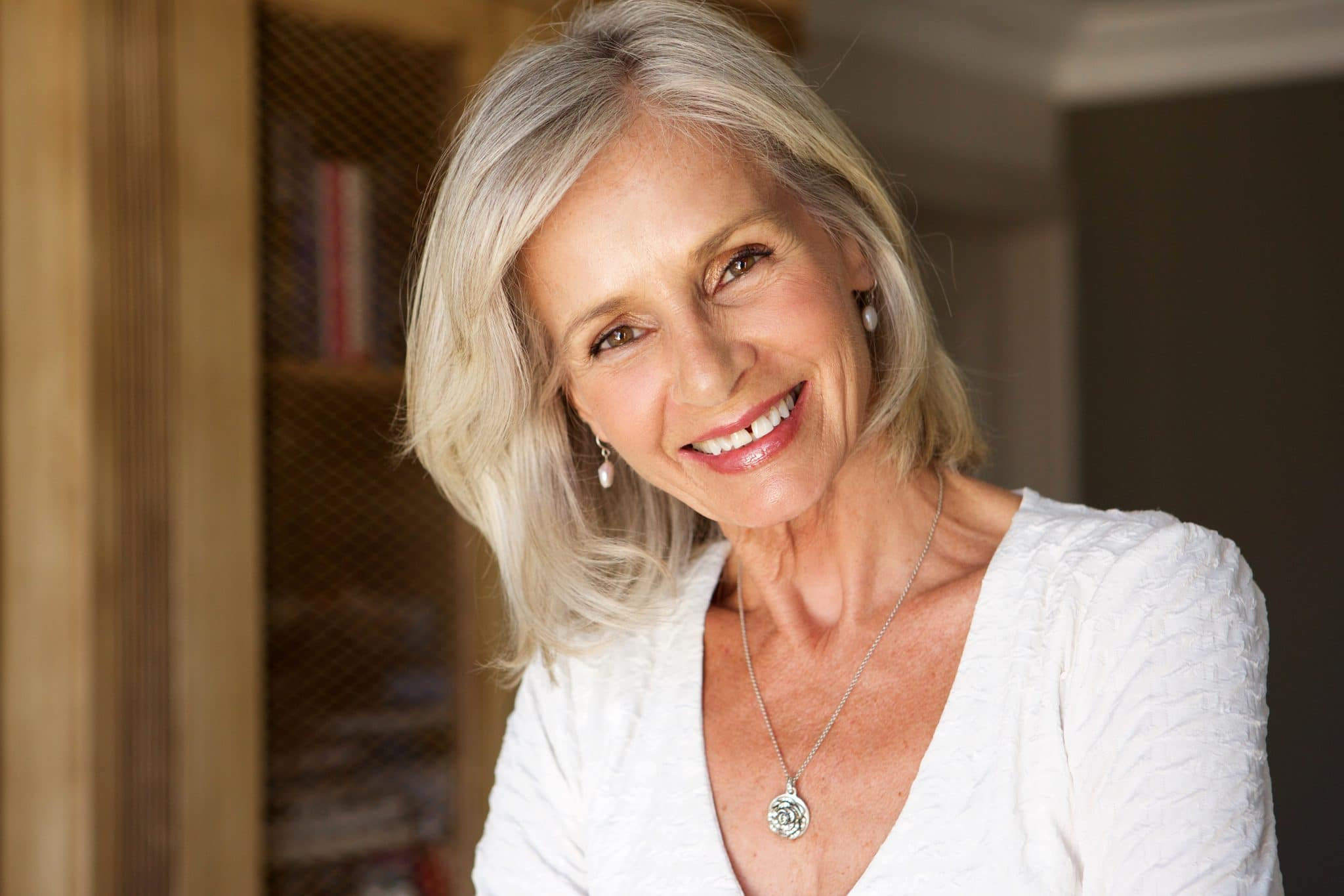Older woman with white shirt on smiling while tilting her head to the side