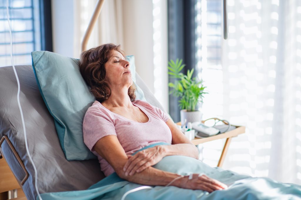 Middle Aged Female Patient Leaning Back on Bed Receiving IV Treatment